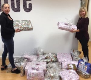 Philomena and Sue with a pile of wrapped donated gifts